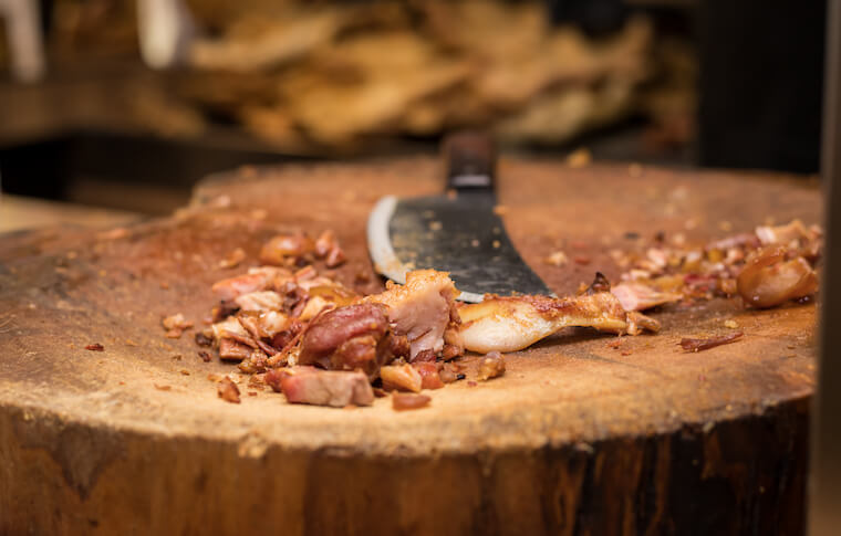 Chopped meat on a wooden block about to fill a Mexican food staple, the taco