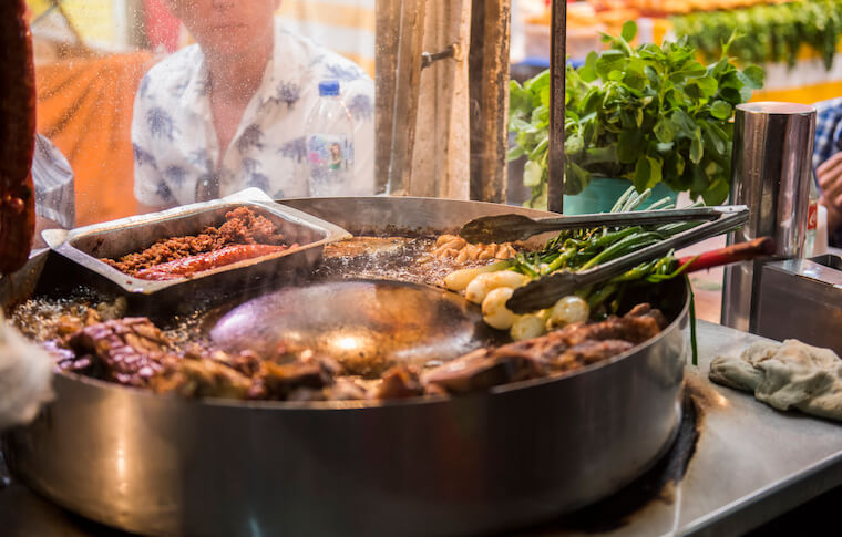 Meat and onions being cooked on a grill at the La Merced market