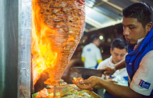 A Mexico City Street food vendor preparing tacos al pastor
