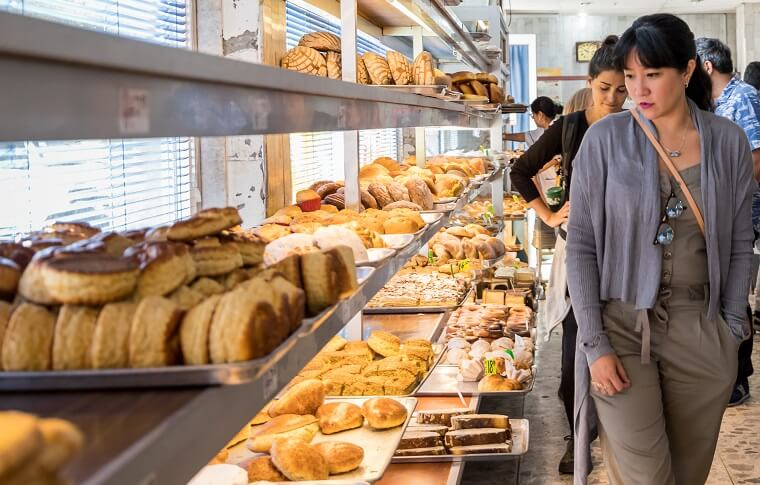 lady looking at bread in bakery