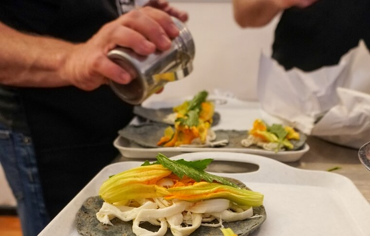 pouring source onto a taco with courgette flower